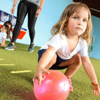 Menina Jogando Bola na Escola de Educação Infantil